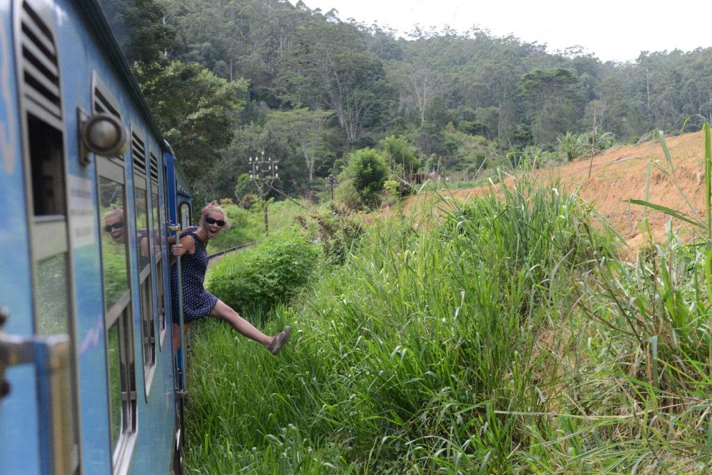 chatoune se penche hors du train par la porte toujours ouverte, entre ella et haputale