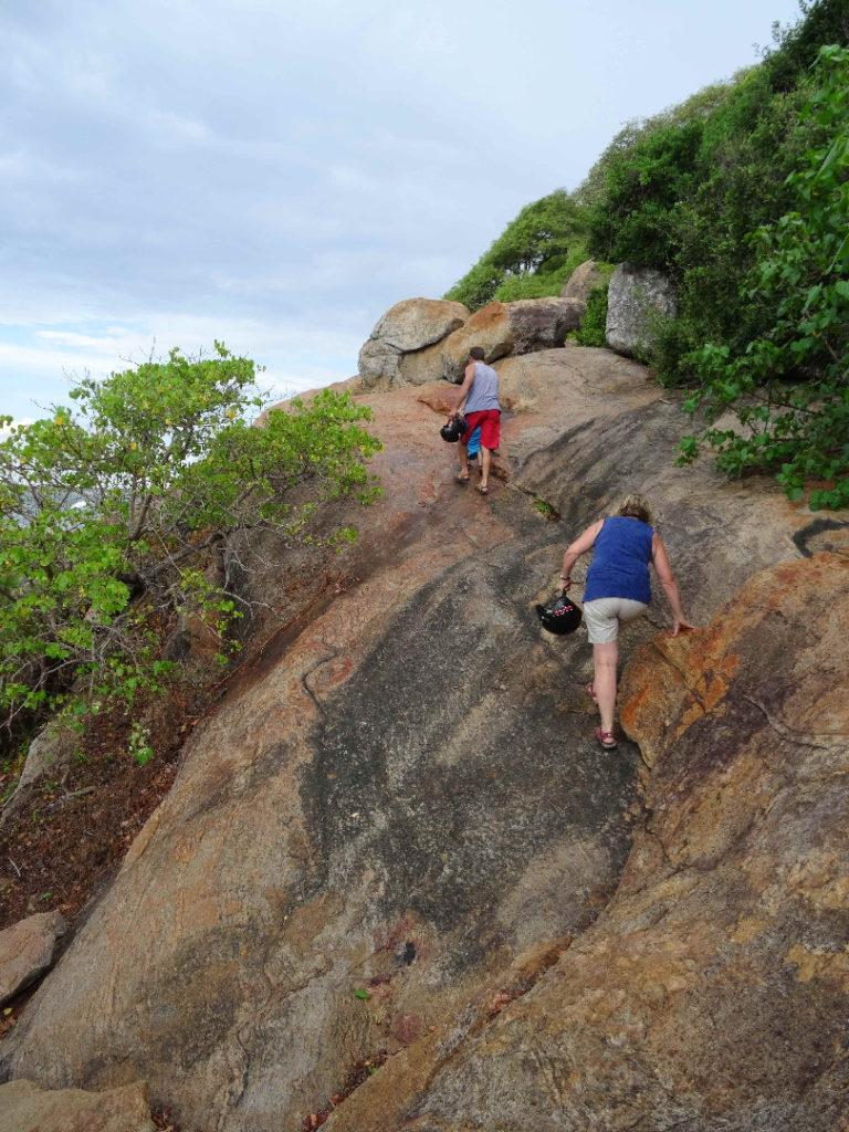 mamisa et chaton grimpent dans les rochers pour accéder à l'entrée d'elephant rock près d'arugam bay
