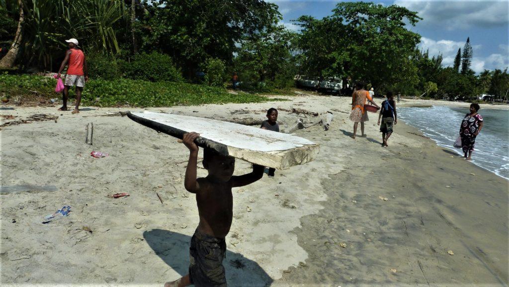 scène de vie plage de mahambo, enfant qui porte une planche sur la tête