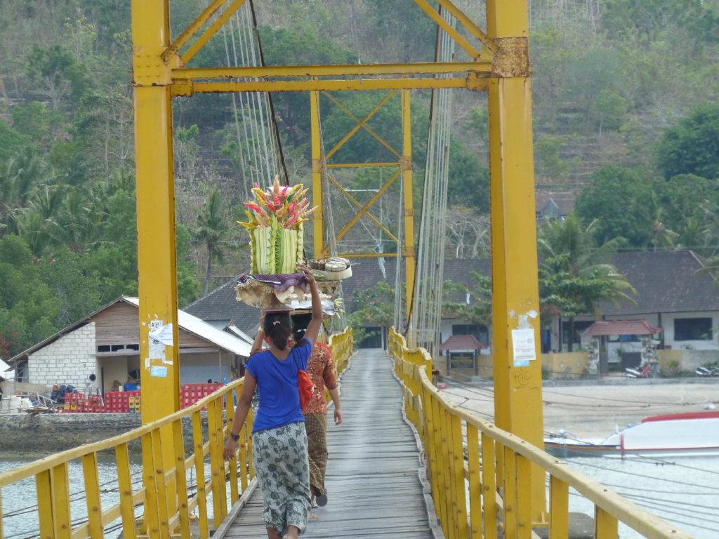 femmes portant des paniers de fleurs sur la route sur le pont entre lembongan et ceningan