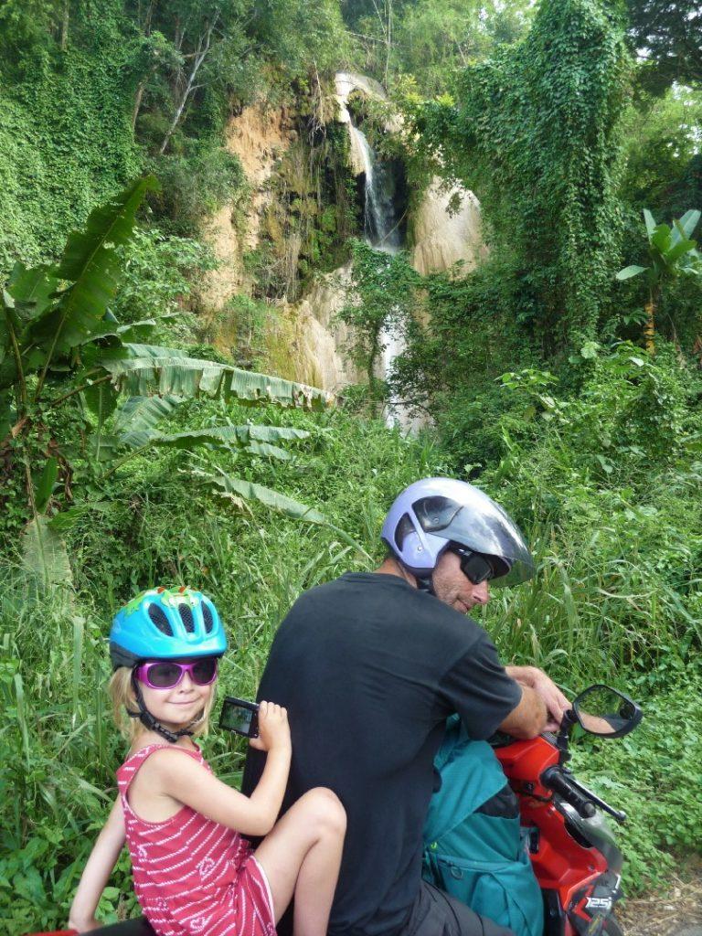 chaton et chatounette à scooter devant une cascade d'eau entre phayao et chiang mai