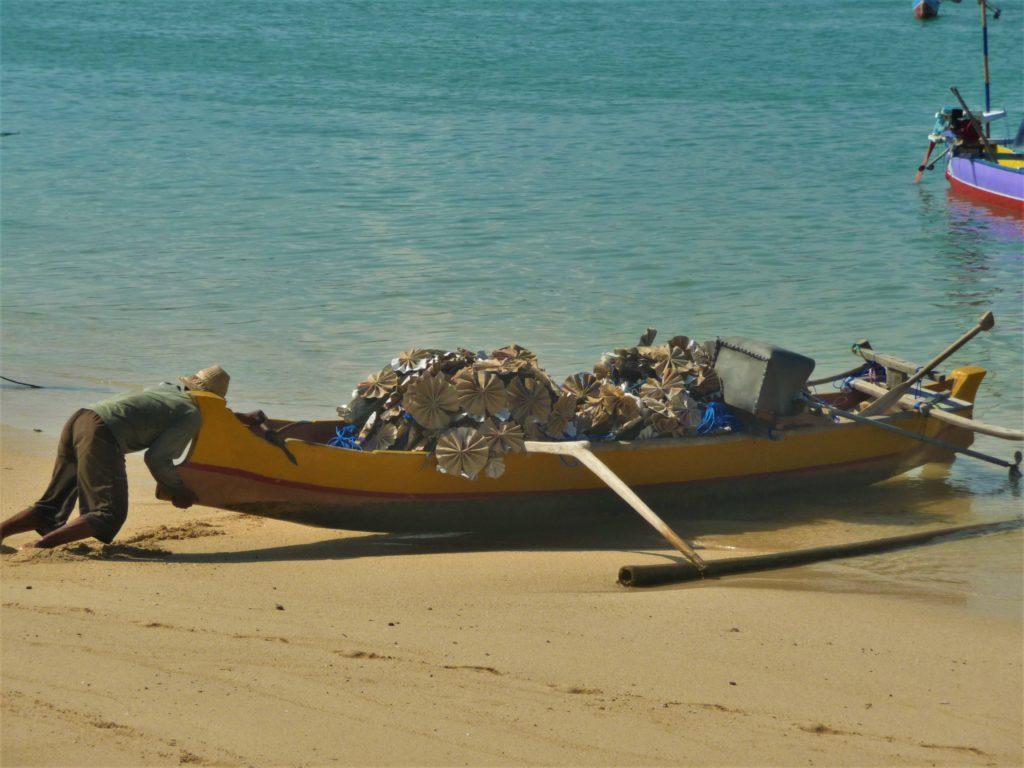 pêcheur en train de mettre son bateau à l'eau sur la plage de Gerupuk, Lombok