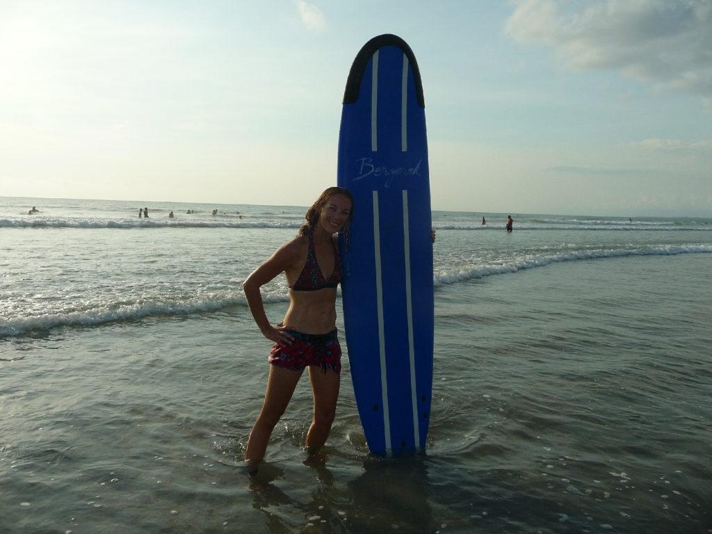 Chatoune avec sa planche de surf sous le bras dans la mer sur la plage de Kuta Bali