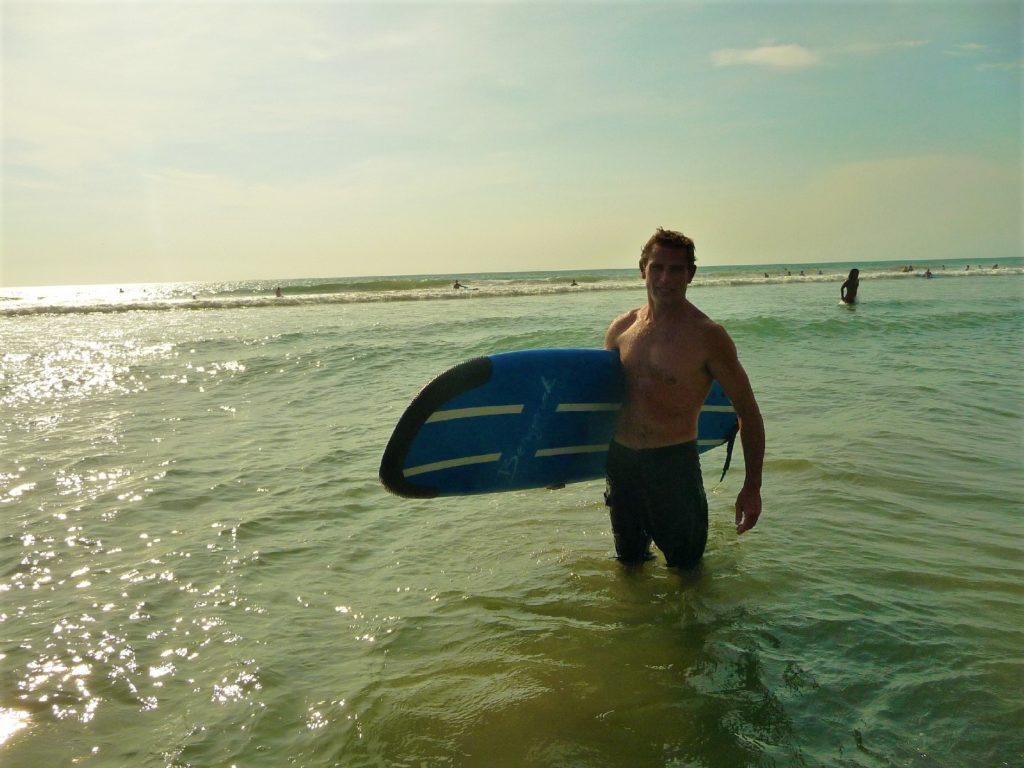 Chaton avec sa planche de surf sous le bras dans la mer sur la plage de Kuta Bali