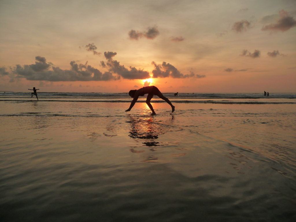 chatoune qui fait des équilibres dans le sable au moment du coucher de soleil sur la plage de Kuta Bali