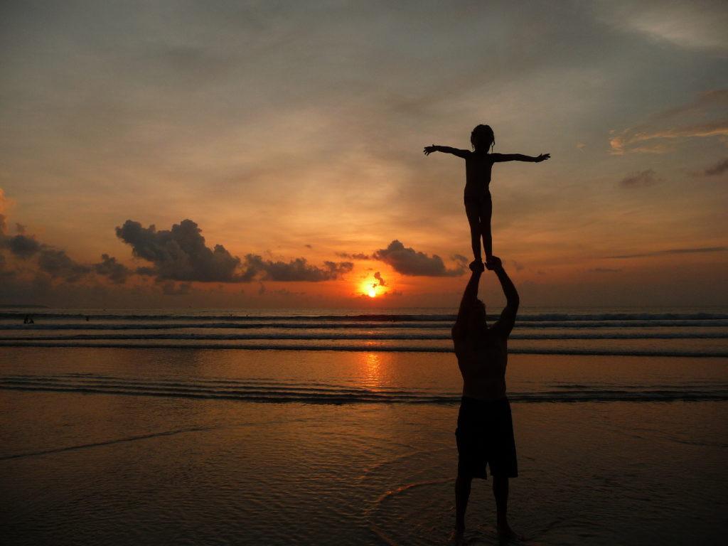 chatounette tient en équilibre sur les bras de Chaton au moment du coucher de soleil sur la plage de Kuta Bali