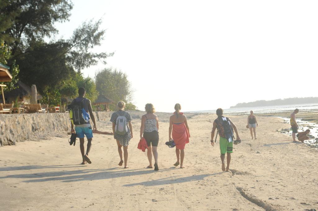 notre troupe de dos marchant sur une plage de gili air