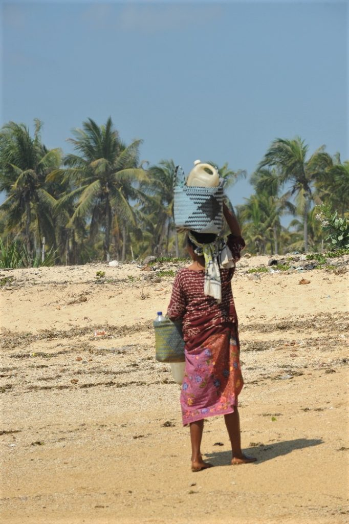 femme portant des objets sur la tête à la plage où ramasser les coquillages entre Kuta Lombok et Tanjung Aan Beach