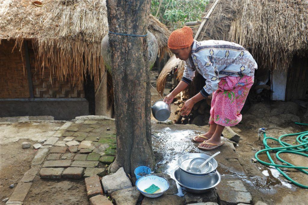 Sade, village sasak à Lombok, femme faisant la vaisselle à la fontaine
