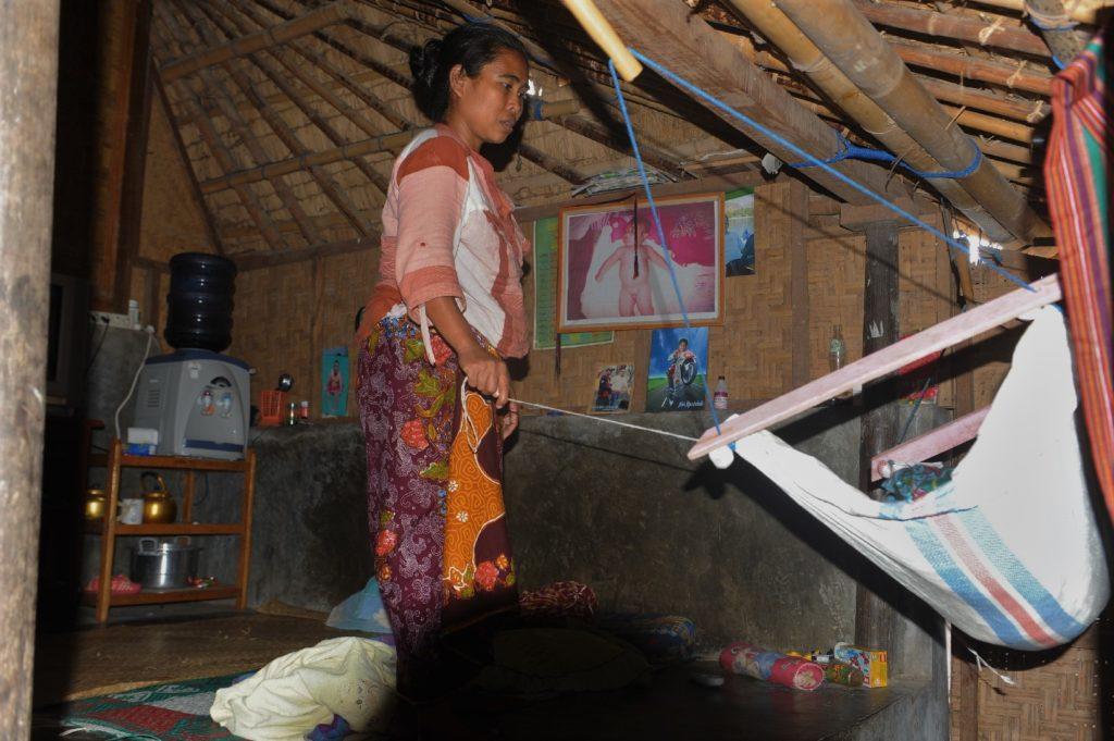 Sade, village sasak à Lombok, femme qui berce son enfant dans sa maison