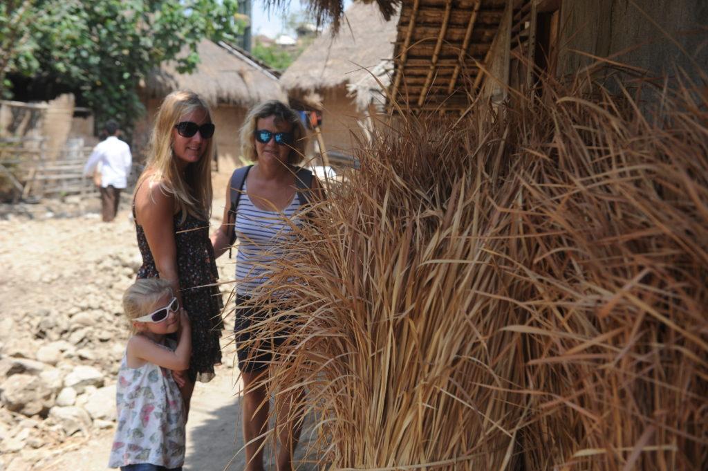 Sade, village sasak à Lombok, pauline, chatounette et mamisa à côté des ballots de paille posés le long d'une maison