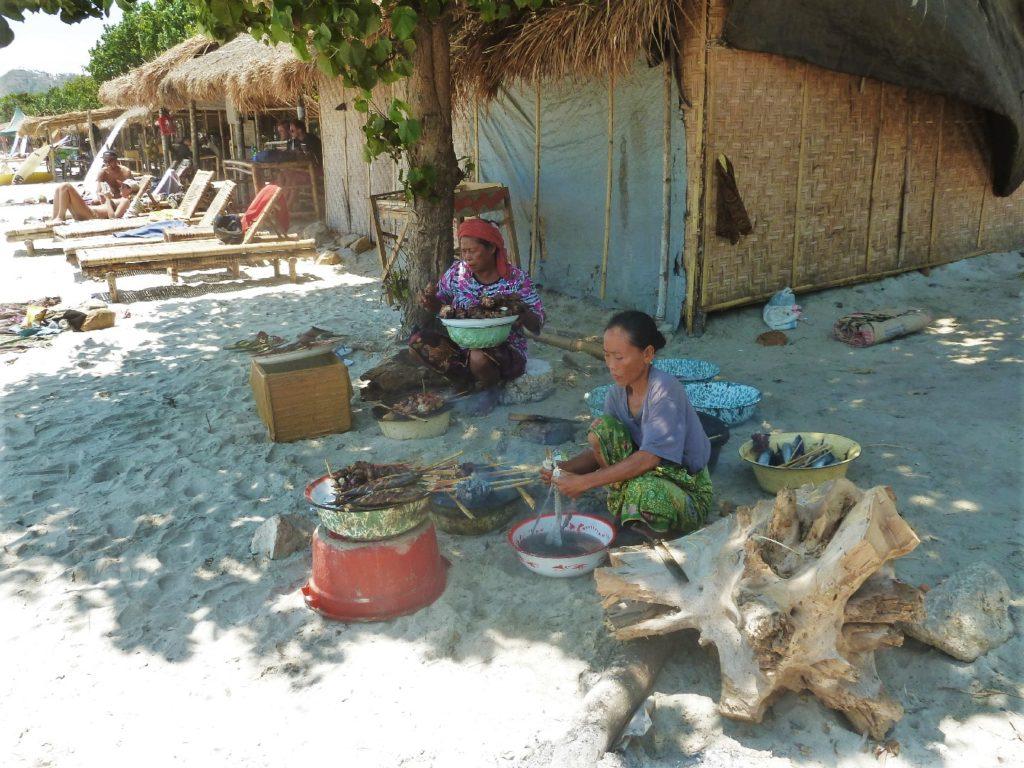 Selong Belanak, plage de rêve de Lombok, au coucher du soleil, femmes faisant griller des brochettes de poissons et calamar