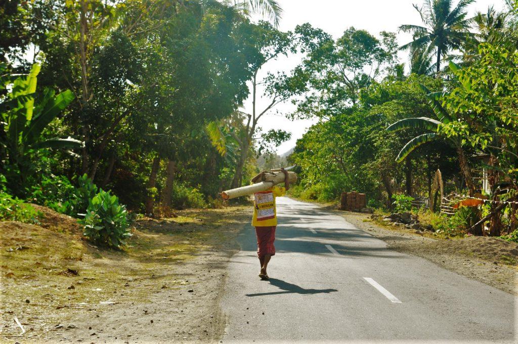 sur la route entre Kuta Lombok et Selong Belanak Beach, personne transportant un grand bambou, pieds nus sur la route