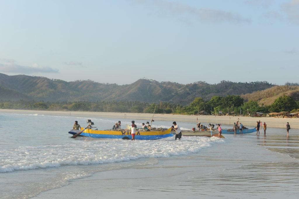 Selong Belanak, plage de rêve de Lombok, au coucher du soleil, pêcheurs mettant le bateau à l'eau