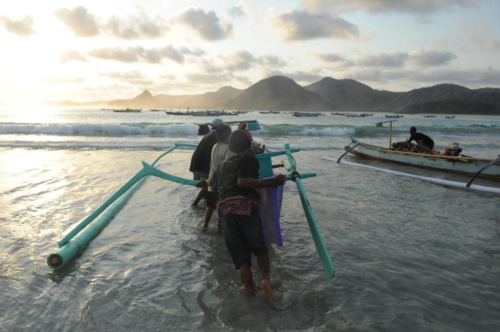 Selong Belanak, plage de rêve de Lombok, au coucher du soleil, pêcheurs poussant le bateau à l'eau