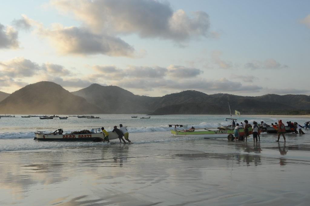 Selong Belanak, plage de rêve de Lombok, au coucher du soleil, pêcheurs partant au large