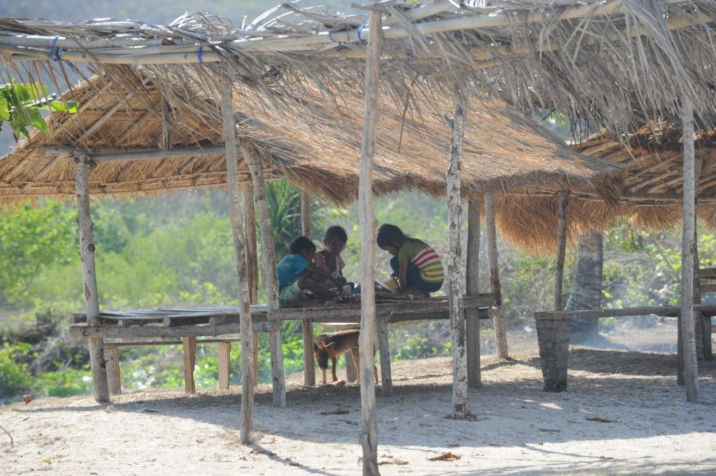 enfants jouant sur un abri en bois sur la plage de Tanjung Aan Beach