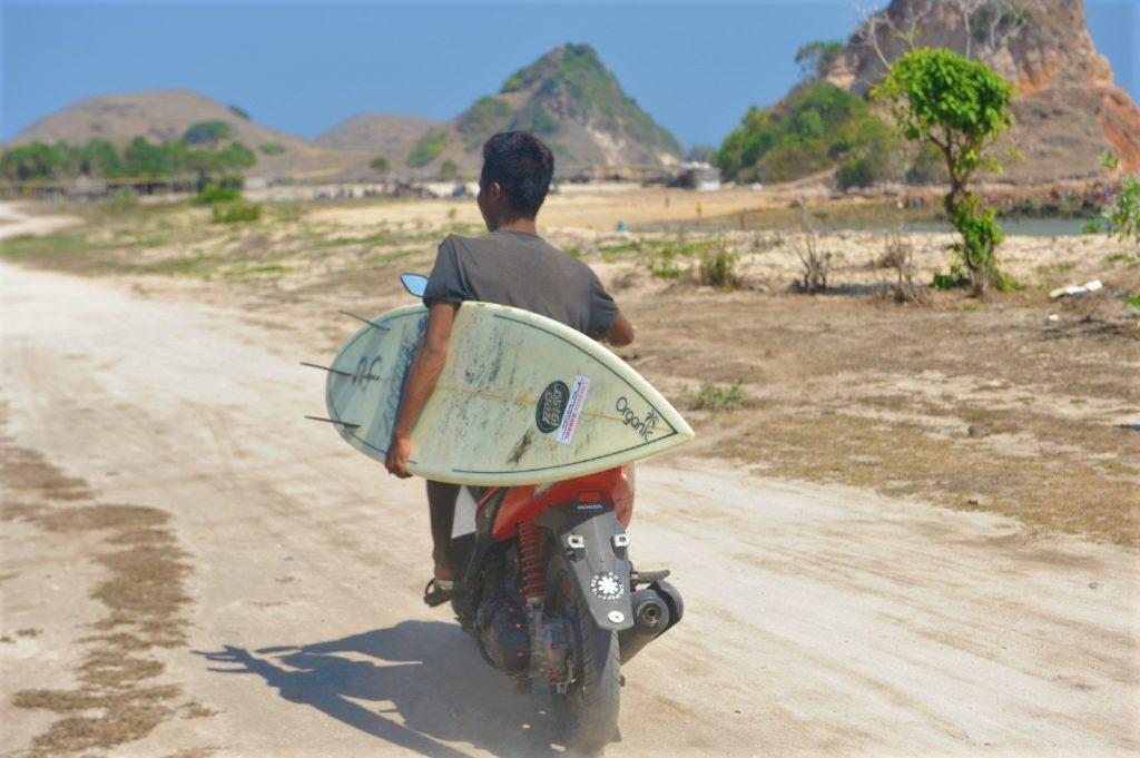 homme sur un scooter tenant une planche de surf sous le bras