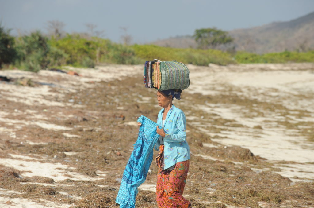 femme portant sur la tête les sarongs qu'elle vend sur la plage de Tanjung Aan Beach