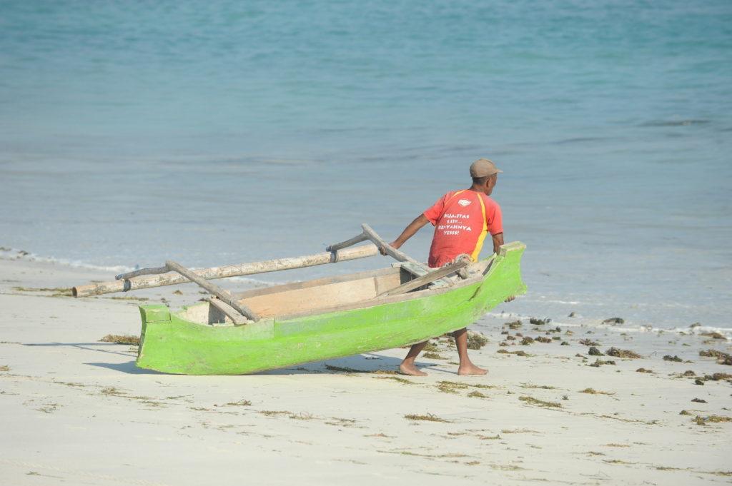 homme mettant son bateau à l'eau depuis la plage de Tanjung Aan Beach