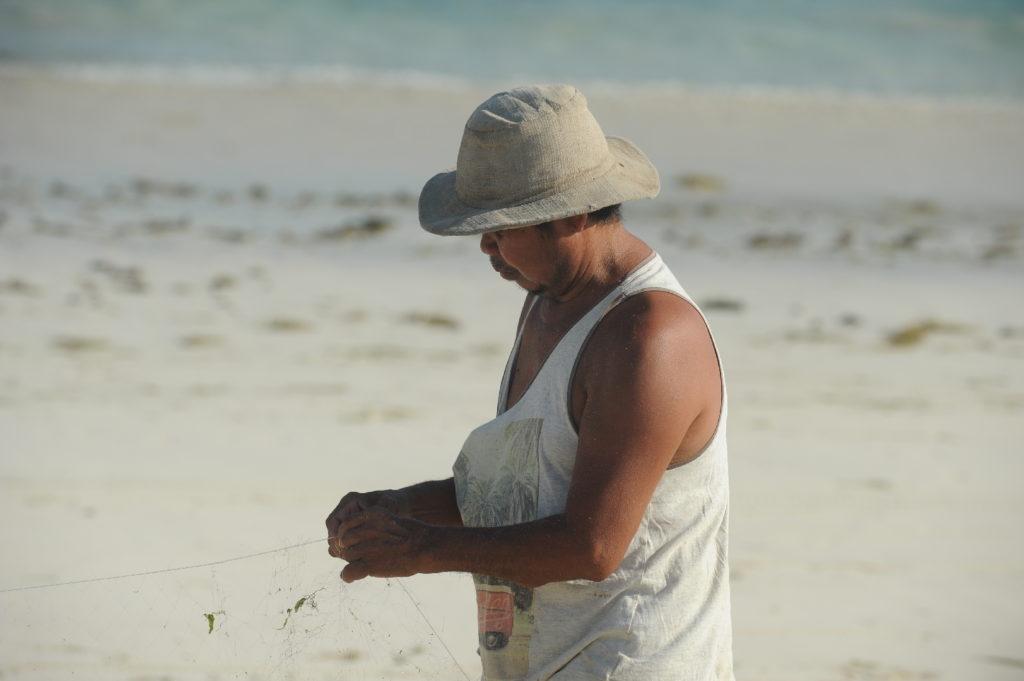 homme préparant son filet de pêche sur la plage de Tanjung Aan Beach