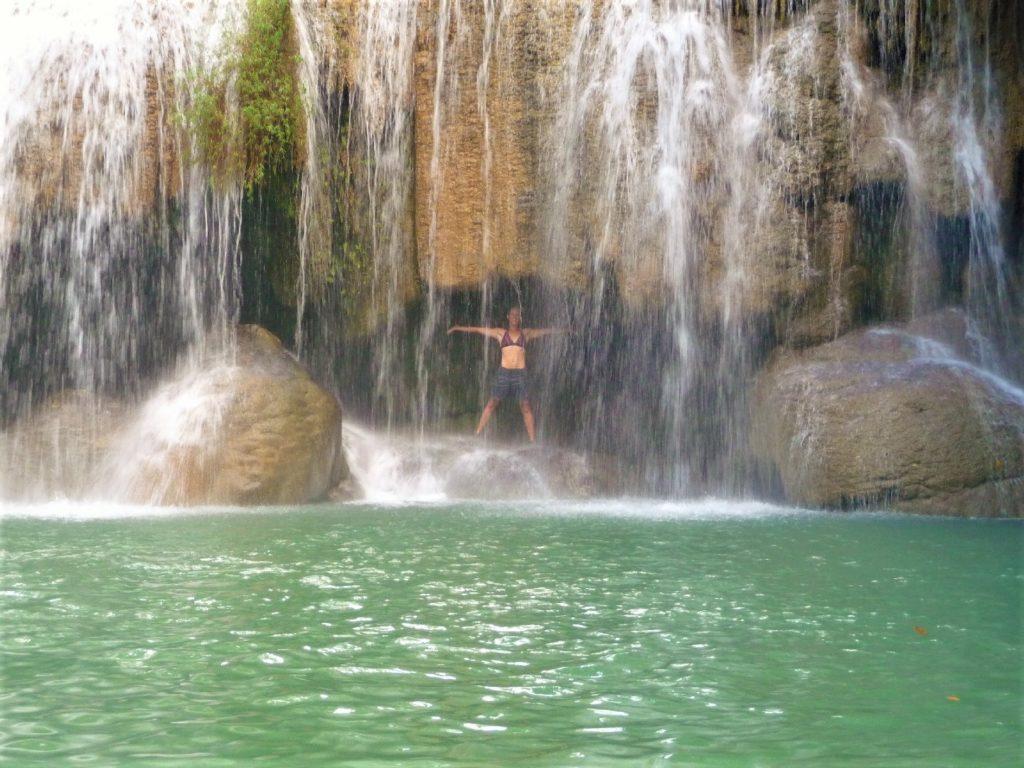 Chatoune derrière le rideau d'eau de la cascade du palier 1, Parc National Erawan, région de Kanchanaburi, Thaïlande