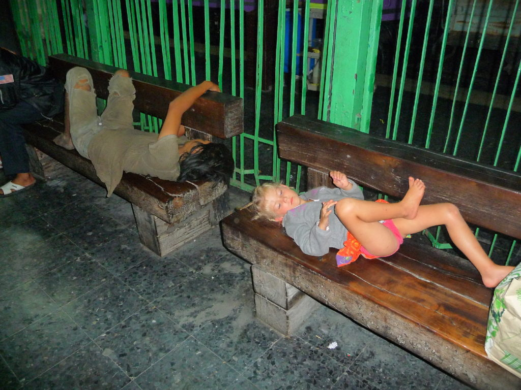 chatounette allongée sur un banc de la gare de bangkok à côté d'un clochard