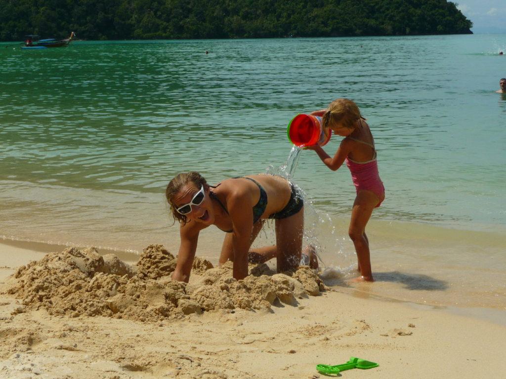 chatounette vide son seau d'eau sur le dos de chatoune, plage de koh phi phi
