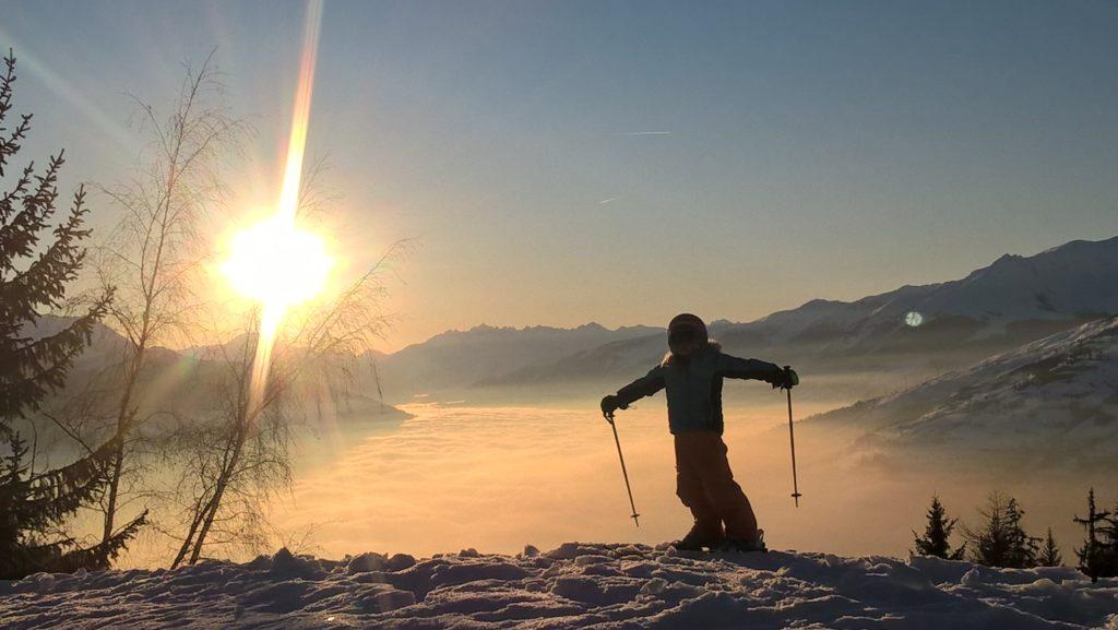 chatounette en ski au coucher de soleil au dessus de la mer de nuage aux arcs