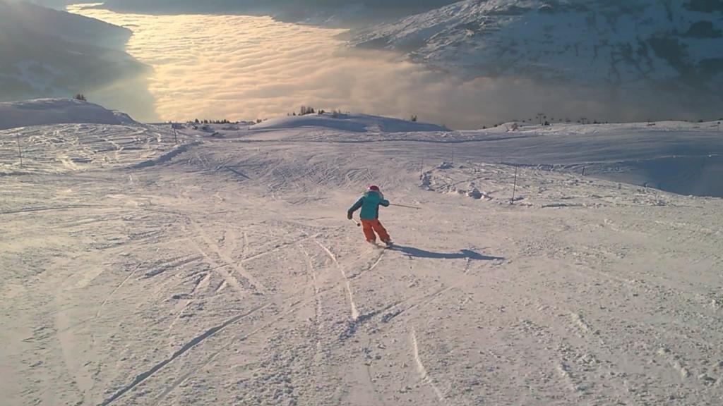 chatounette skiant au coucher de soleil au dessus de la mer de nuage aux arcs